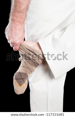 A man removing his socks shows several inferences regarding dexterity and daily tasks adults conduct.