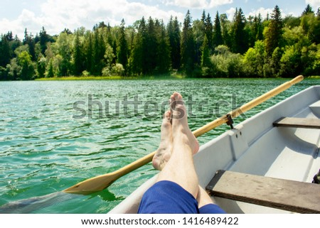 A man resting in a boat in the middle of a beautiful lake