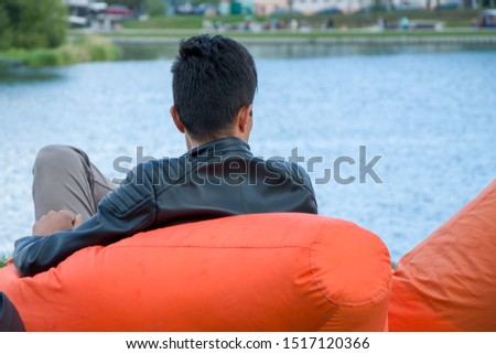 A man rests in an orange armchair-bag looking at the water surface, the rest of the weekend in nature