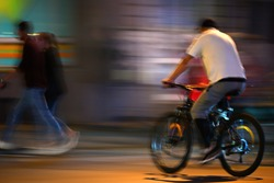 A man rides a bicycle on a night street. A blurred image enhances the effect of motion.