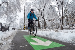 A man rides a bike in the winter along the bike path. Eco-friendly mode of urban transport