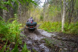 A man rides an ATV rear view. Riding an Quadrocycle through mud. Off-road travel. Concept is the lack of roads. Extreme sports. Concept - sale of ATVs and accessories. Quadrocycle stuck in the mud