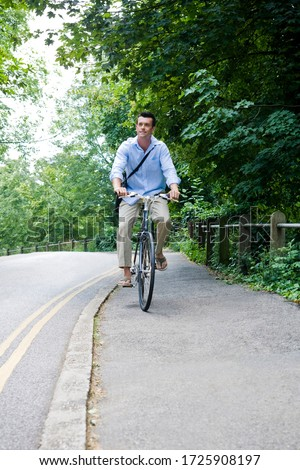 A man riding a bicycle along a country road