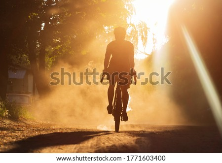 Photo of  A man riding a bicycle on a gravel road at sunset. A silhouette of a cyclist on a gravel bike in a cloud of dust.