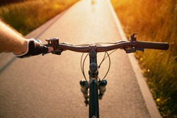 A man riding a bike. Holding bike handlebar with one hand in a sports glove with sunlight at the top. Concept of summertime outdoor leisure sport activity. First-person view bicycle riding.