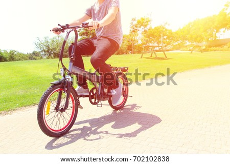 A man riding on electric bicycle in a park #702102838