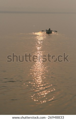 A man rows a boat at sunrise on the Ganges River in India