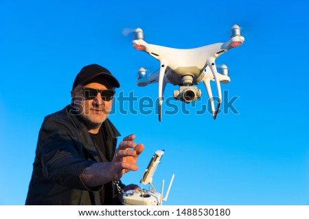 A man runs a quadrocopter. Drone with the ability to take photos and videos. Remote control of the quadcopter. The launch of an unmanned aerial vehicle. Flight control.