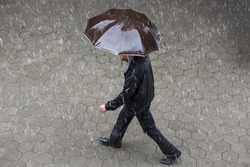 A man runs in the rainy weather with hir brown umbrella. Raining like cats and dogs. Bad weather. Climate change.