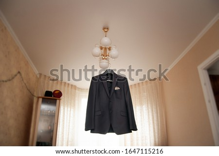 A man's black jacket hangs on a lamp in the living room. Groom's morning