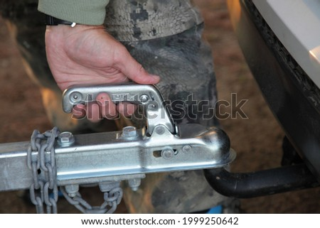 A man's hand checks the fixation of the trailer closed hitch lock handle on the towing ball towbar of the car closeup, the safety of driving with a trailer on the road Foto stock ©