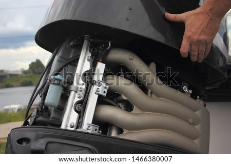 A man's hand closes the hood of a powerful outboard boat motor, repair and maintenance of boat engines, a view of the intake manifold of a four-cylinder four-stroke injector motor