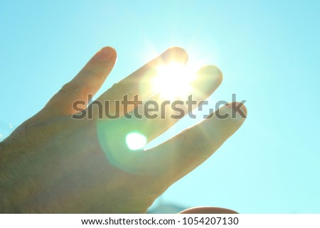 A man's hand covering the sunlight. The sun shines through the hand. Background.