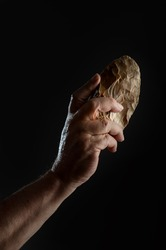 A man's hand holding a bifacial-backed knife. Knife carved in flint from the Middle Paleolithic, on black background
