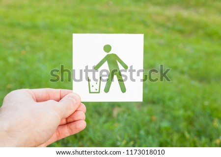 A man's hand holding a paper with a garbage tank symbol carved into it. Ecology, recycling of garbage, conservation of nature. #1173018010