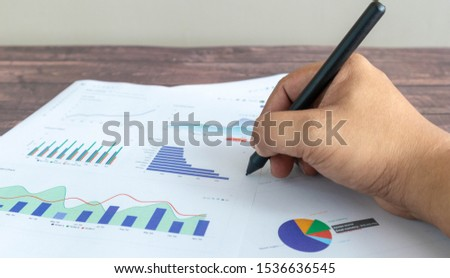A man's hand holding a pen is about to write something on the line graph, circle graph, and various color chart graphs printed on a white paper. Placed on a wooden patterned work desk