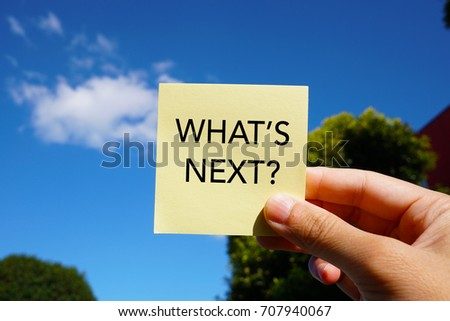 A man's hand holding a yellow sticky notes with words on the blue sky and white background. WHAT'S NEXT?
