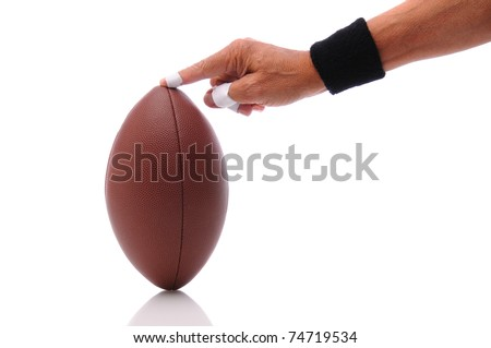 A man's hand holding an american football ready for place kicking. Horizontal format isolated on white with reflection.