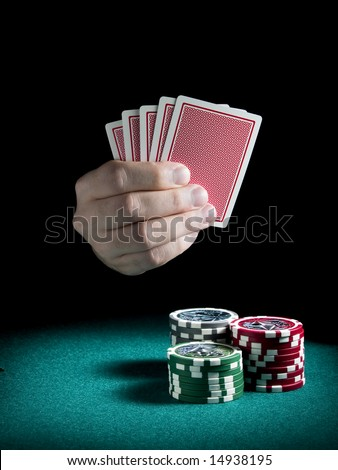 A man\'s hand holding four cards over three piles of different colors chips on a green felt.