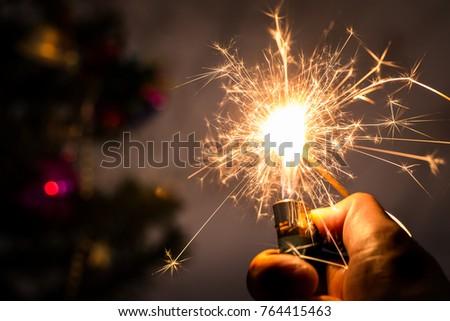 A man's hand holding lighter burning Christmas sparkler. #764415463
