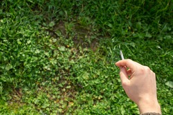 A man's hand holds a cigarette against a background of bright green grass.