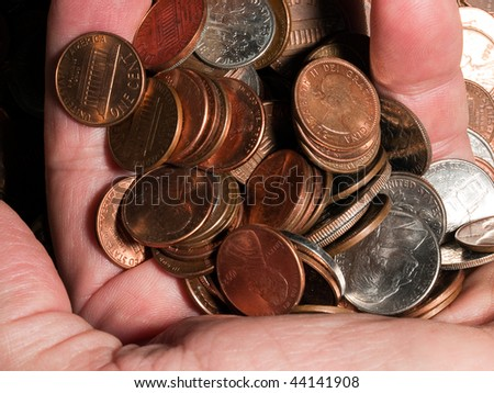 A man's hand holds a fist full of copper and silver money coins