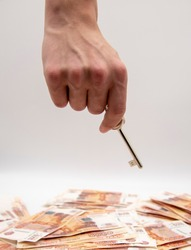 A man's hand holds a key over a pile of five-thousand-ruble bills.The concept of improving housing conditions, buying an apartment or mortgage.