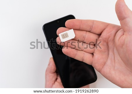 a man's hand holds a SIM card near a black smartphone. subscriber's electronic module used in mobile communications. 4G Internet Photo stock ©