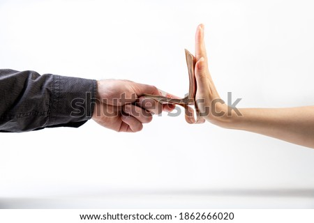 A man's hand in a black shirt gives a stack of money to a woman's hand, which refuses. Side view. White background. The concept of the world anti-corruption day Сток-фото ©