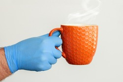 A man's hand in a medical glove holds a cup of hot drink. The doctor drinks coffee. The patient drinks hot medicine. Anti virus protect concept. A man in protective medical gloves holds a orange e cup