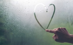 A man's hand is writing a heart-shaped glass window during a rain.