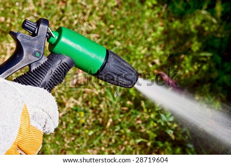 A man's hand keeping a spouting sprinkler at the garden.