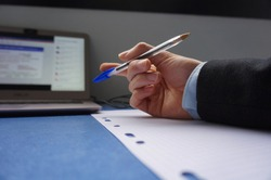A man's hand on a desk, above a sheet of paper, holds a blue ballpoint pen. The person wears a suit, and plays with the pen handled between his fingers ; there is a computer in the background