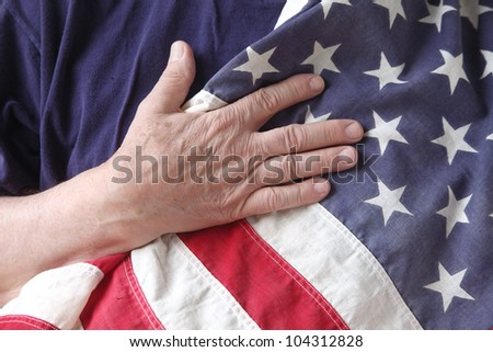 a man's hand on a USA flag against his chest