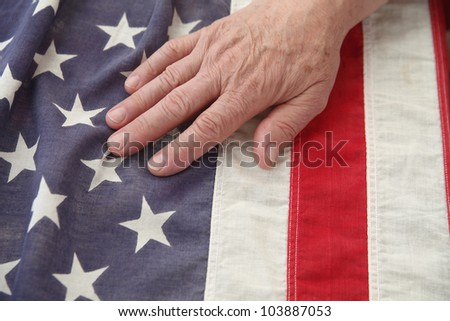 a man's hand on a very old American flag