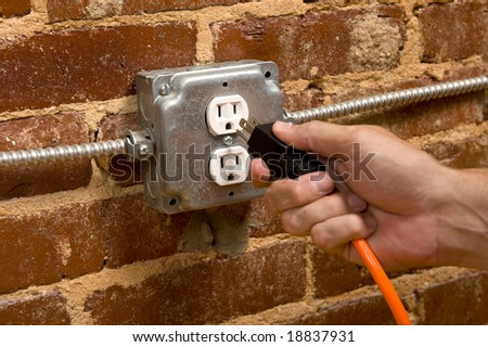 a man's hand plugging in an extension cord in  a junction box electrical outlet on a brick wall, connecting concept