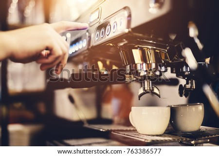 A man's hand pressing the button on a coffeemaker. A white cup standing beneath.