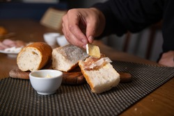 A man's hand putting a delicious brie cheese slice on the top of a french baguette sandwich with butter and parma ham preparing breakfast or brunch on a rustic table in his home kitchen