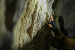 A man's hand touches a wall in a karst cave inside the Mangup plateau in the Crimea, near the city of Bakhchisarai. Travel, adventure, hiking, motivation and speleology concept.