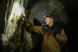 A man's hand touches a wall in a karst cave inside the Mangup plateau in the Crimea, near the city of Bakhchisarai. A man with backpack is dressed in a brown windbreaker. Head torch on.