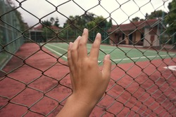 A man's hand touches the fence of a tennis court that is being closed and is quiet because of the lockdown period.