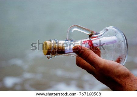 A man's hand with a glass vessel against the sea #767160508