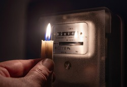 A man's hand with candle in complete darkness looking on electricity meter at home. Power outage, blackout concept.