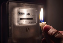 A man's hand with candle in complete darkness near an electricity meter at home. Power outage, blackout, non-payment of electricity bill concept.
