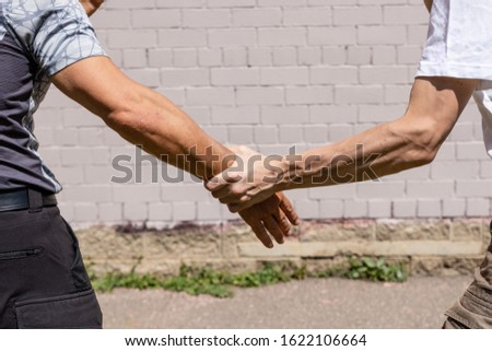 A man's hand with pale skin holds a tanned man's hand by the wrist. Martial arts instructors demonstrate self-defense techniques of Krav Maga