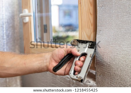 A man's hand with the help of a construction stapler fastens onto a wooden beam a foil-insulated heater for the sauna, against the window. Close-up.