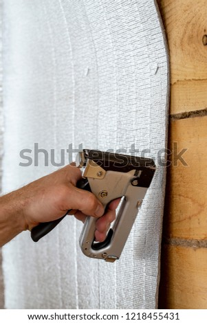 A man's hand with the help of a construction stapler is attached to a wooden beam with foil insulation for a sauna. Close-up.