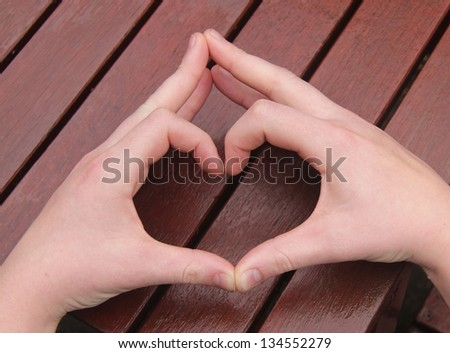 A man's hands make heart sign on wooden background
