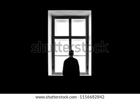 A man's silhouette in front of the window. Black and white. Concept of loneliness and isolation.  #1156682842