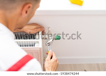 A man saws off a pipe with a circular saw, flying sparks, replacement of the radiator in the apartment, plumbing work Photo stock ©